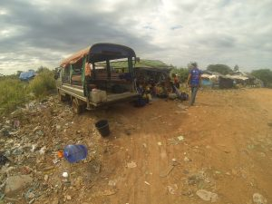 The bus parks up on the dump where the children gather