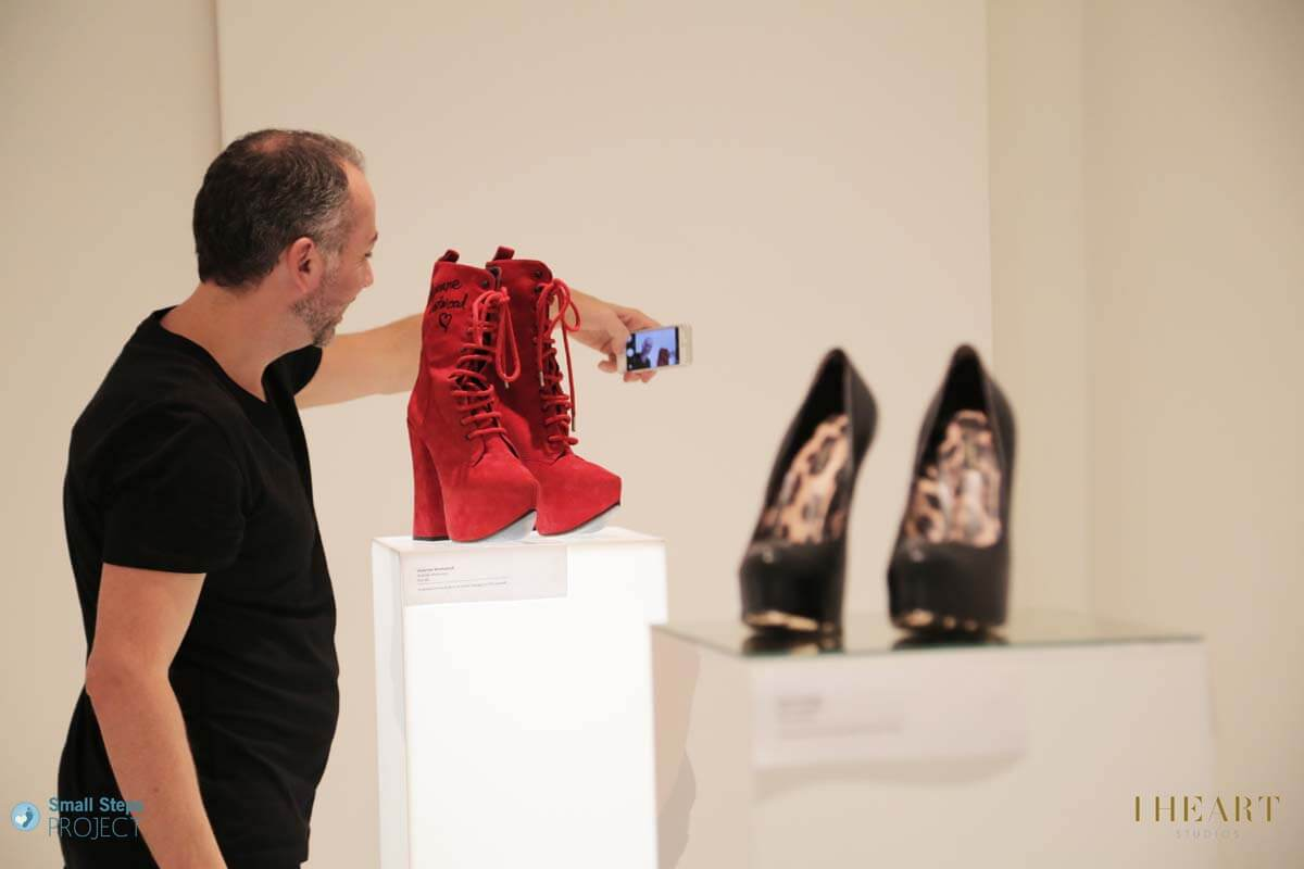 A guest taking a selfie with Vivienne Westwood's boots.
