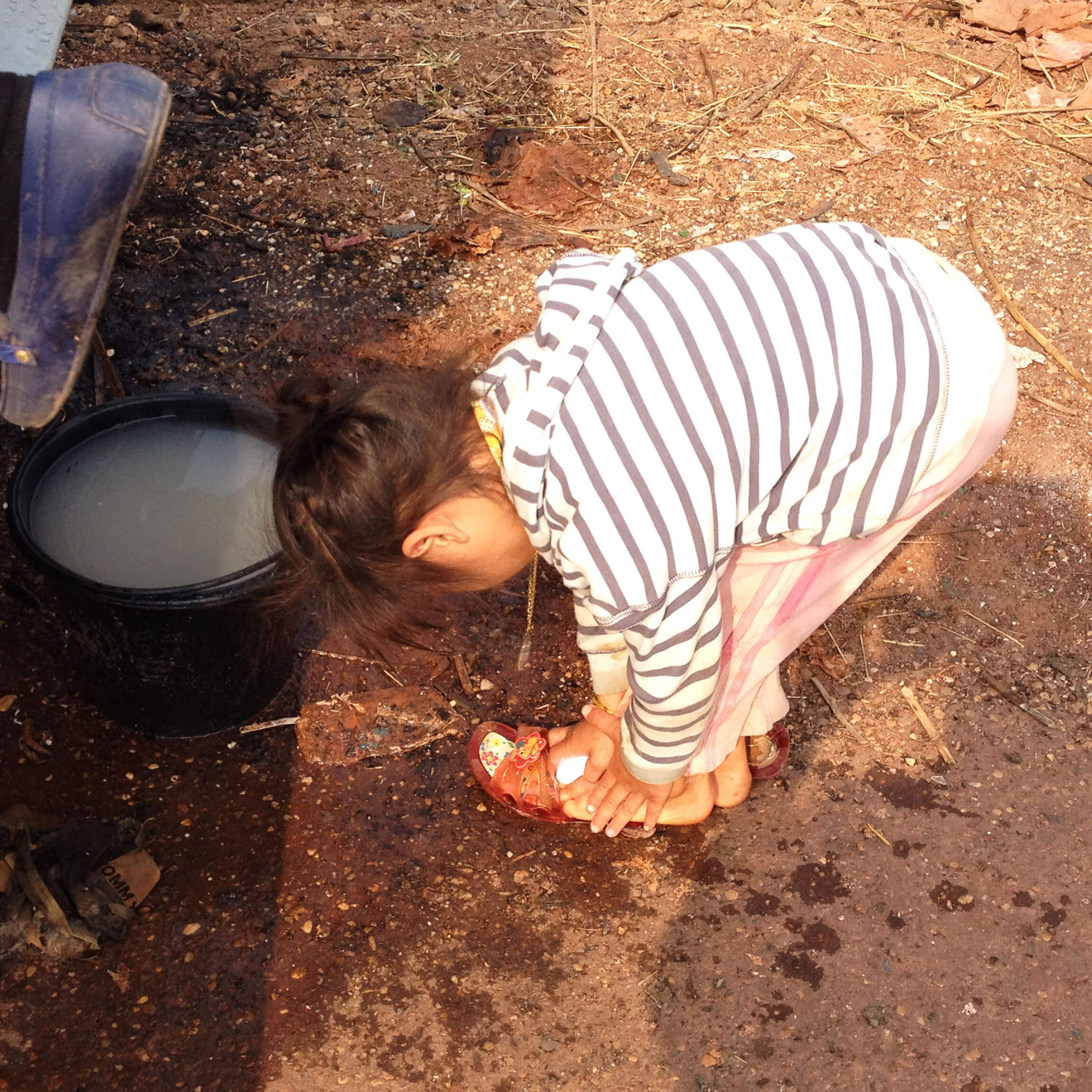 A young girl washes her feet with water and soap provided by the mobile school.