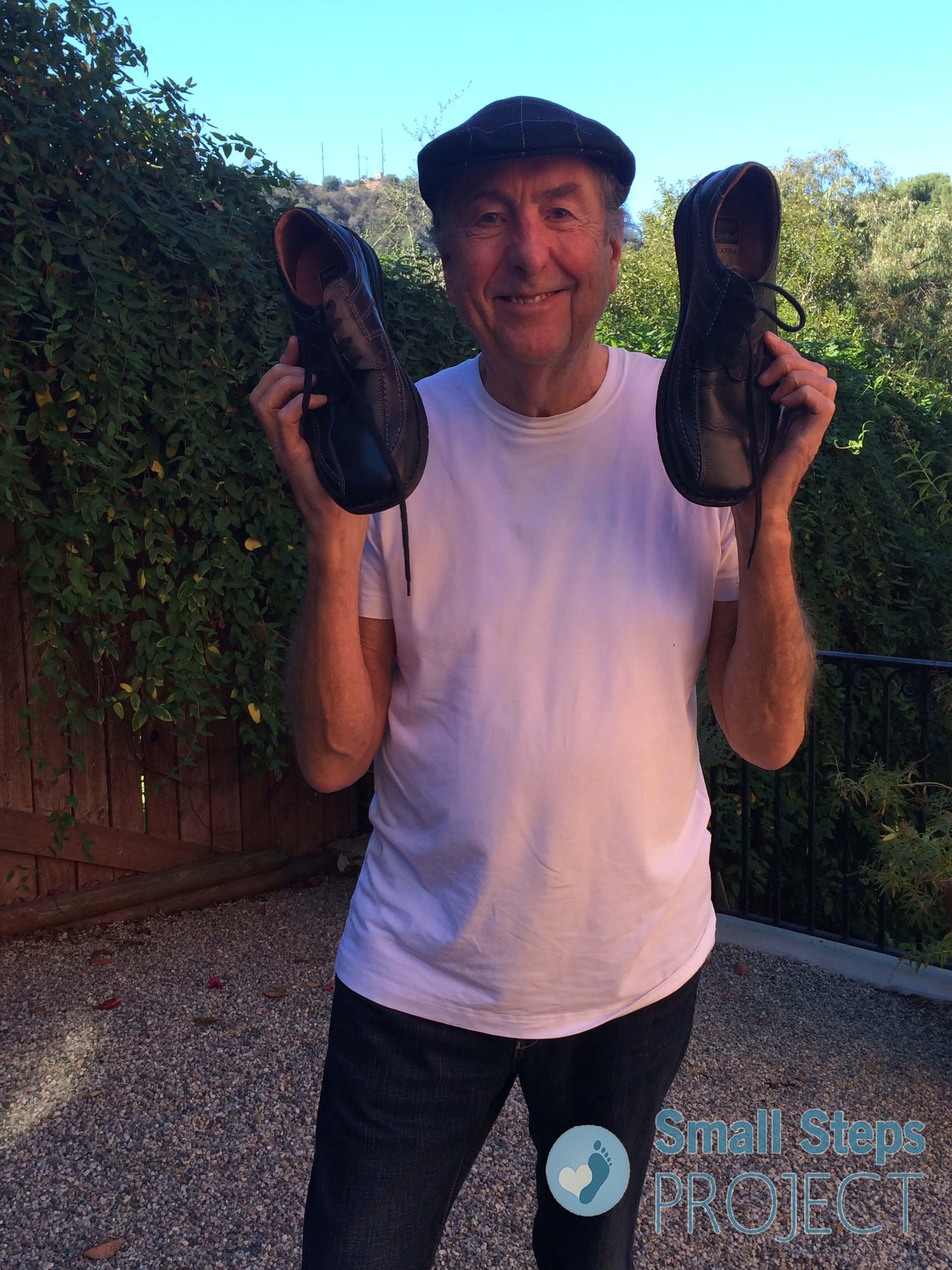 Eric Idle with his donated shoes 2015
