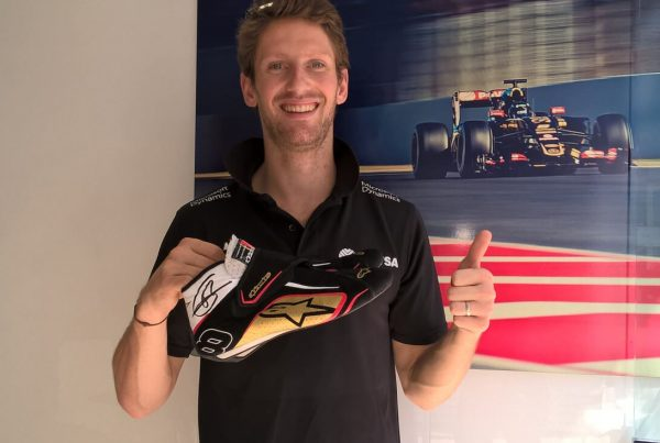 Romain Grosjean holding his donated pair of shoes!